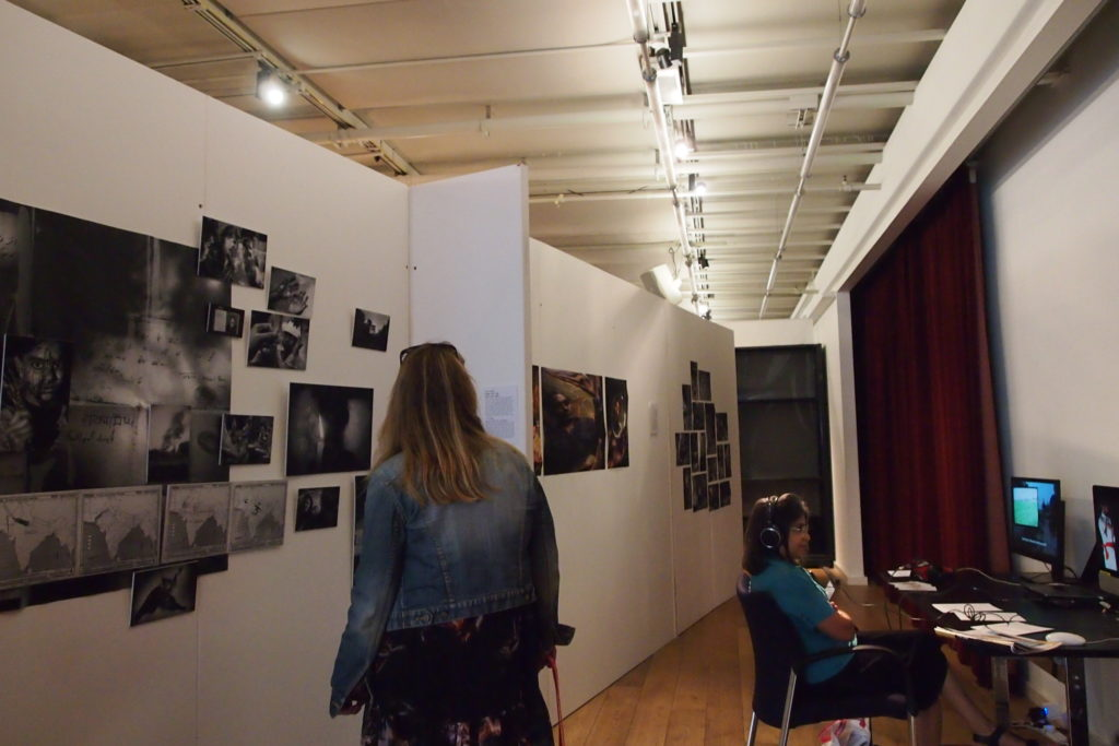 Viewers watching photographs and films created during the September/October Creative Interruptions grant in Preet Nagar at British Film Institute, London